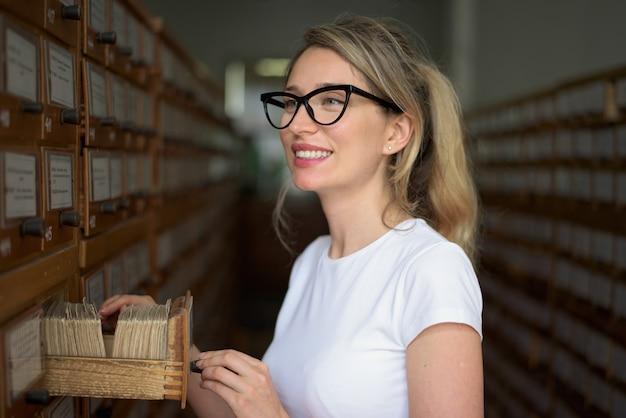 Blondevrouw die boekdossiers in oude catalogus zoeken
