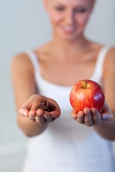 Blondevrouw die chocolade en appeldrank op chocolade en appel tonen