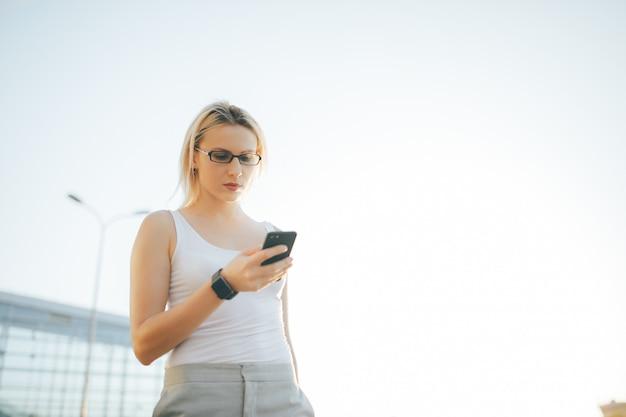 Blondevrouw die een bericht op de telefoon lezen