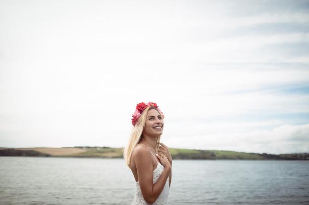 Blondevrouw die een bloementiara dragen die zich dichtbij een rivier bevinden
