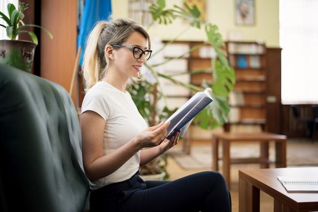 Blondevrouw die een boek in bibliotheek lezen