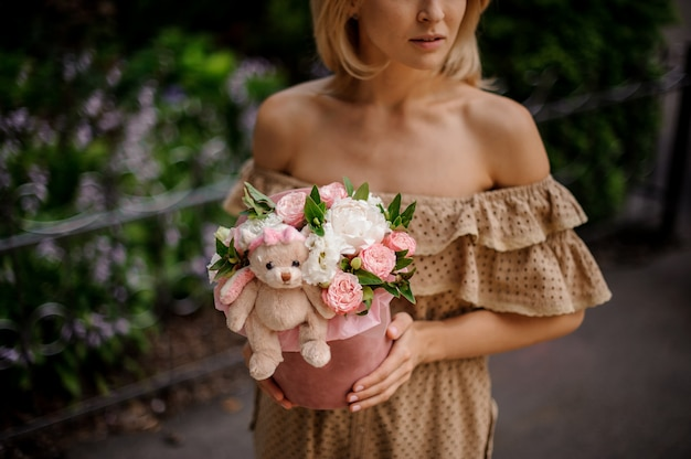 Blondevrouw die een doos houden die met bloemen wordt gevuld