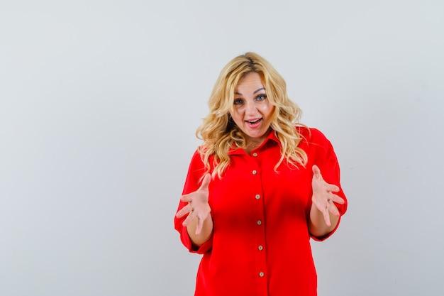 Blondevrouw die één hand uitrekt als iets in rode blouse ontvangt en gelukkig, vooraanzicht kijkt.