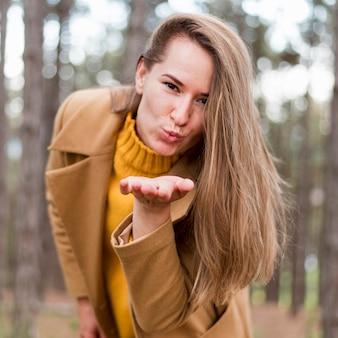 Blondevrouw die een kus blazen