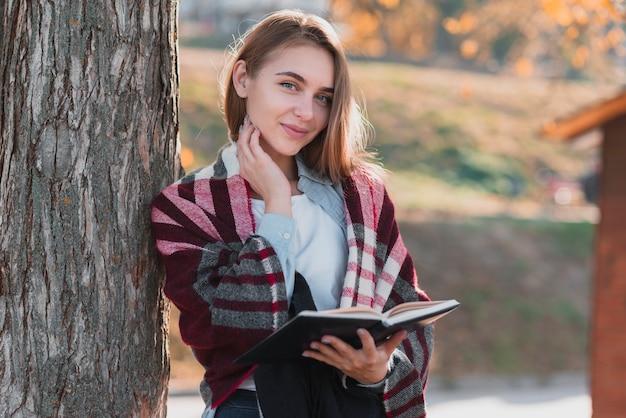 Blondevrouw die een notitieboekje houden en fotograaf bekijken