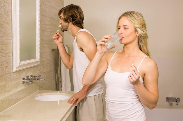 Blondevrouw die een pil met haar vriend nemen die zijn tanden thuis in de badkamers borstelen