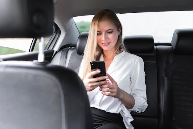 Blondevrouw die een telefoon in de auto met behulp van