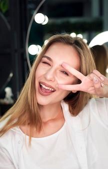 Blondevrouw die en vredesteken glimlachen doen