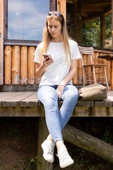 Blondevrouw die haar telefoon bekijken