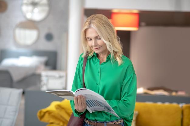 Blondevrouw die in een groene blouse het kiezen van nieuw meubilair kijken