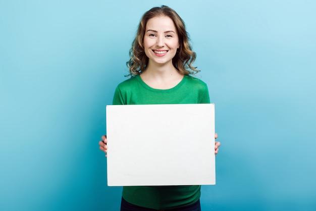 Blondevrouw die in groene sweater dragen die een ruimte van het wit raadsexemplaar houden tegen blauwe muur