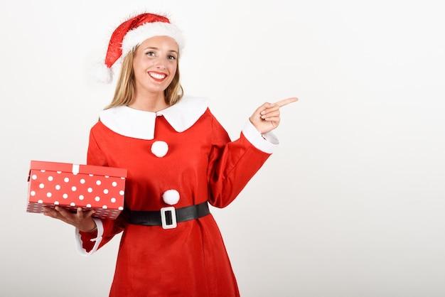 Blondevrouw die in santa claus-kleren met giftdoos glimlachen.