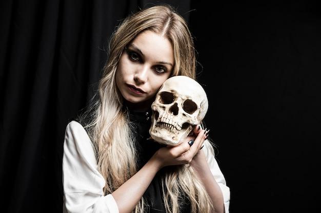 Blondevrouw die menselijke schedel houden