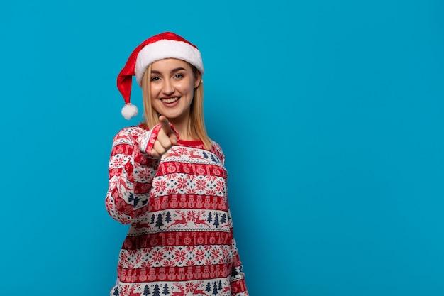 Blondevrouw die met santahoed op camera met tevreden, zelfverzekerd richten