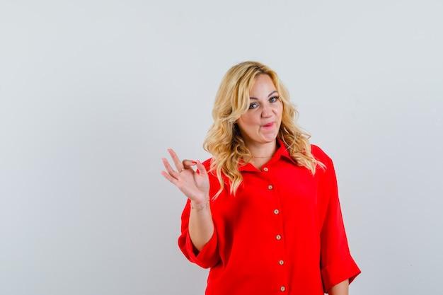 Blondevrouw die ok teken in rode blouse tonen en gelukkig kijken