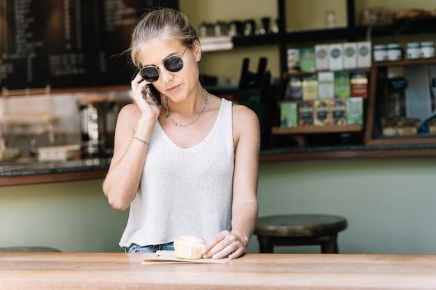 Blondevrouw die op haar mobiele telefoon met een kaneelbroodje bij een cafetaria spreken