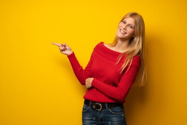 Blondevrouw die over gele muur vinger aan de kant in zijpositie richten