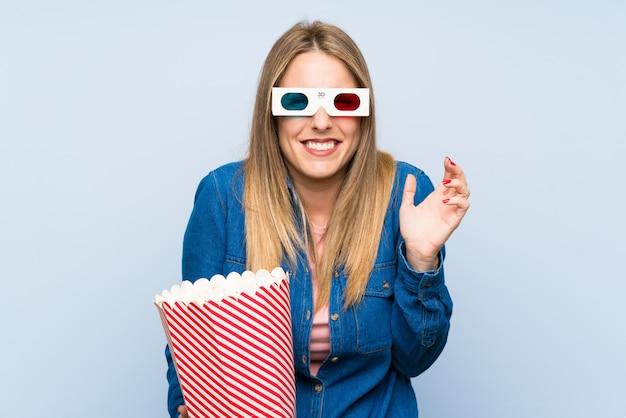Blondevrouw die popcorn eten ongelukkig en gefrustreerd met iets. negatieve gelaatsuitdrukking
