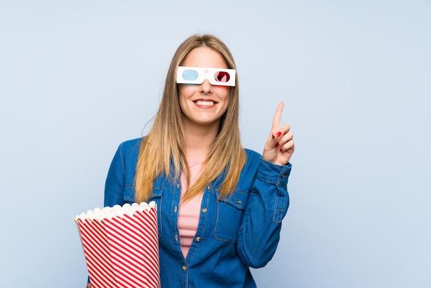Blondevrouw die popcorns eten die met de wijsvinger richten een groot idee