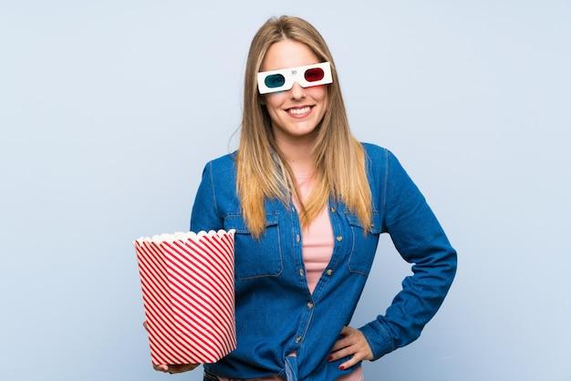 Blondevrouw die popcorns eten die met wapens stellen bij heup