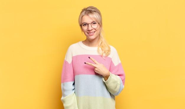 Blondevrouw die zich gelukkig, positief en succesvol voelt, met hand die v-vorm over borst maakt, overwinning of vrede toont