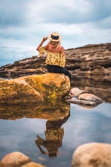Blondevrouw in een bloemenoverhemd bij de rotsen