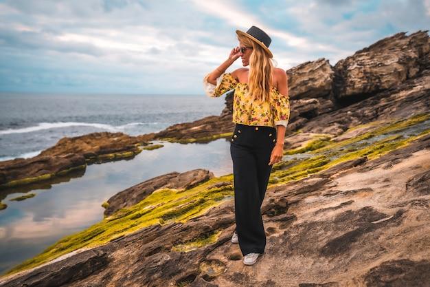 Blondevrouw in een bloemenoverhemd bij het rotsachtige strand