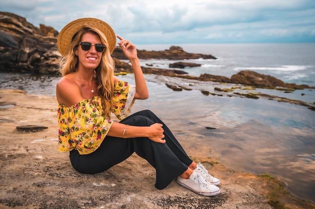 Blondevrouw in een bloemenoverhemd bij het strand