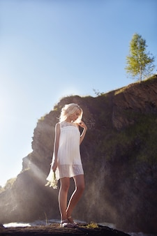 Blondevrouw in een witte kleding en bloemenmadeliefjes in haar hand