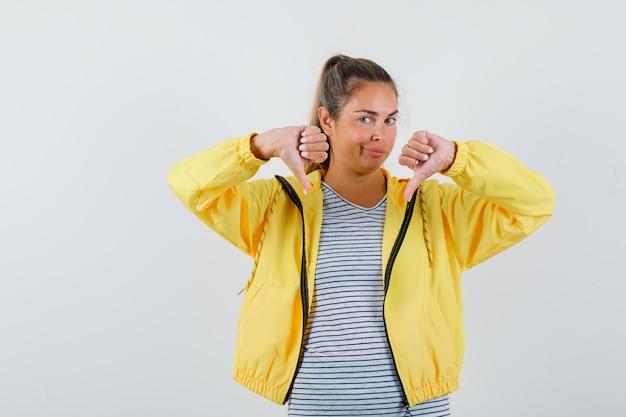 Blondevrouw in geel bomberjack en gestreept overhemd die duimen neer met beide handen tonen en mooi kijken