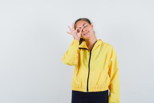Blondevrouw in geel bomberjack en zwarte broek die ok teken op oog tonen en gelukkig kijken