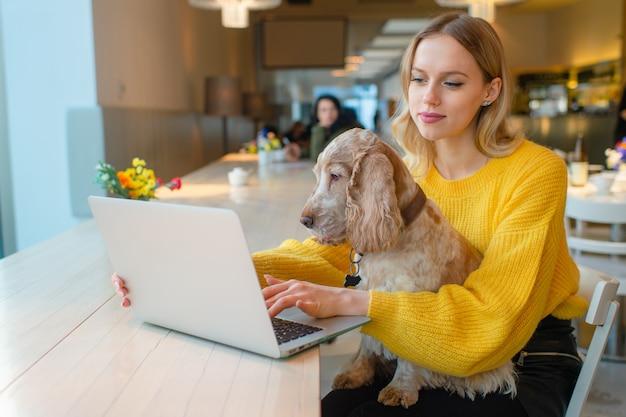 Blondevrouw in geel sweatshirt die aan laptop in medewerkruimte werken en haar oude cocker-spaniëlhond op haar knieën houden