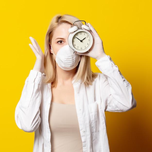 Blondevrouw in gezichtsmasker en wekker op gele muur