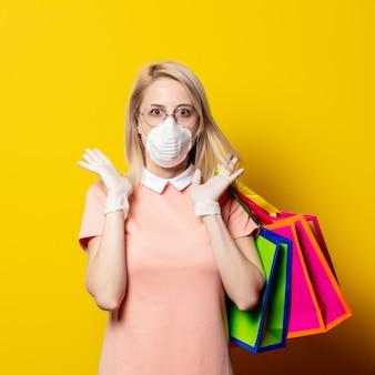 Blondevrouw in gezichtsmasker met het winkelen zakken op gele muur