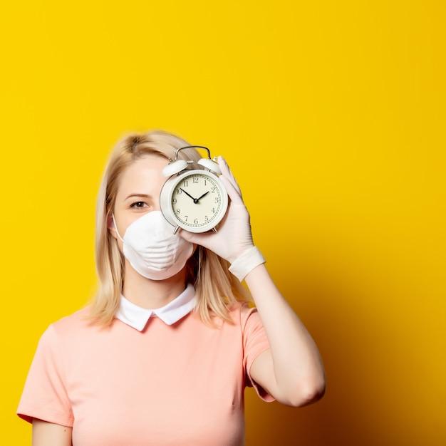 Blondevrouw in gezichtsmasker met wekker op gele muur