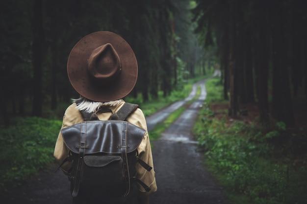 Blondevrouw in hoed met rugzak in regenachtige dag in bos