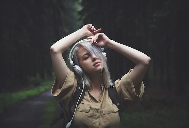 Blondevrouw in hoofdtelefoons met rugzak in regenachtige dag in bos