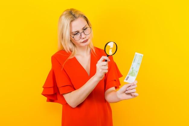 Blondevrouw in kleding met vergrootglas