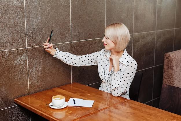 Blondevrouw in koffie die selfie met mobiele telefoon nemen