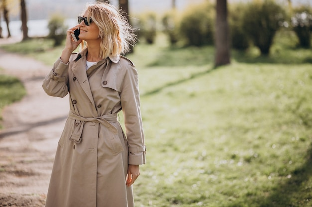 Blondevrouw in laag buiten in park die telefoon met behulp van