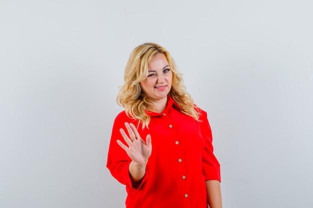 Blondevrouw in rode blouse die stopbord toont en knipoogt en gelukkig, vooraanzicht kijkt.