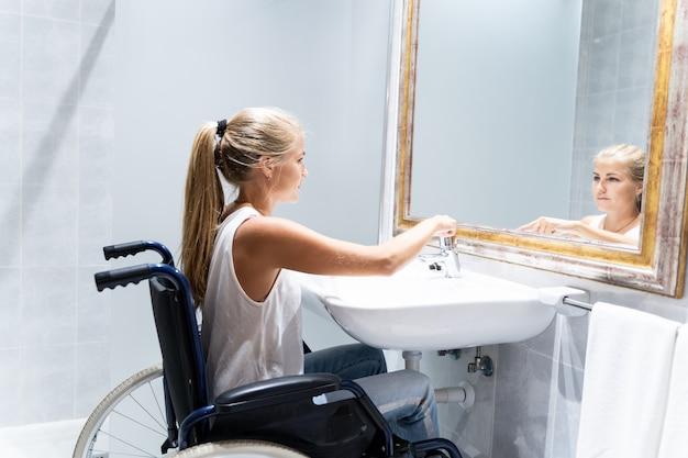 Blondevrouw in rolstoel die het water in een badkamers aanzetten