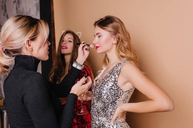 Blondevrouw in zwart overhemd die make-up voor krullend vrouwelijk model doen