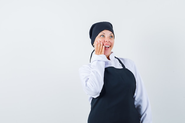 Blondevrouw in zwarte uniforme kok die hand op wang zet en verbaasd kijkt