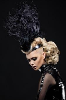Blondevrouw met artistiek kapsel en make-up, in sexy zwarte kleding en hoed met veer