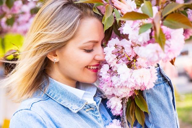 Blondevrouw met bloeiende sakura-boom en zonnige dag. lentebloemen met blauwe achtergrond en wolken.