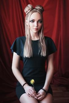 Blondevrouw met grote blauwe ogen zoals een elf, lang wit haar in een knot, een meisje met kapsel en make-up in een groene jurk op een rood ogende