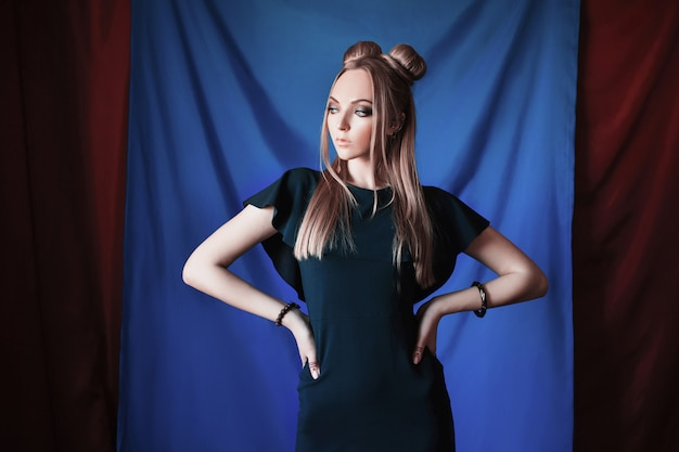 Blondevrouw met grote blauwe ogen zoals een elf, lang wit haar in een knot, een meisje met kapsel en make-up in een zwarte jurk