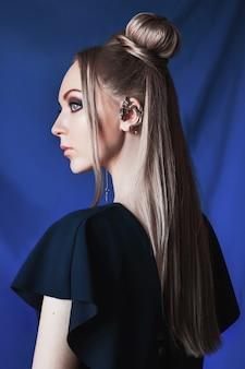 Blondevrouw met grote blauwe ogen zoals een elf, lang wit haar in een knot, een meisje met kapsel en make-up