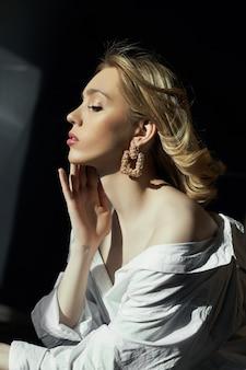 Blondevrouw met juwelenoorringen in hun oren in de stralen van de avondzon.